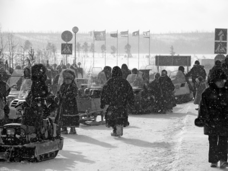herder: Nadym, Russia - March 11, 2005: the national holiday, the day of the reindeer herder in Nadym, Russia - March 11, 2005. Snowmobiles parked on the roadside. Strangers near snowmobiles.