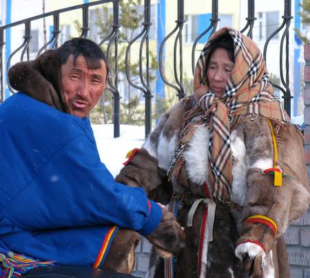 herder: Nadym, Russia - March 11, 2005: the national holiday, the day of the reindeer herder in Nadym, Russia - March 11, 2005. Unknown man and woman - Nenets sitting in the street. Editorial