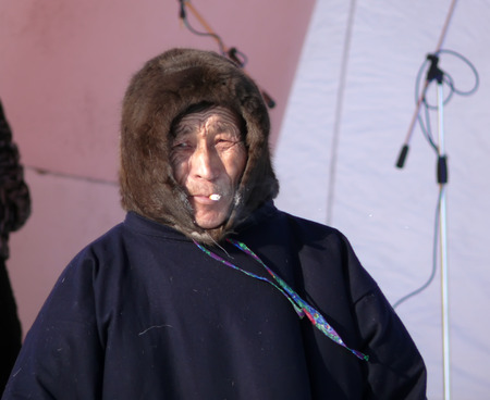 herder: Nadym, Russia - March 15, 2008: the national holiday - the Day of the reindeer herder in Nadym, Russia - March 15, 2008. Unknown man Nenets on the stage and smokes.