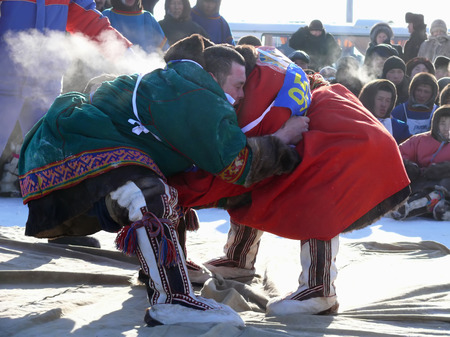 unknown men: NADYM, RUSSIA - March 15, 2008: National Holiday - Day of the reindeer herders. The wrestling unknown men on holiday in Nadym, Russia - March 15, 2008. Editorial