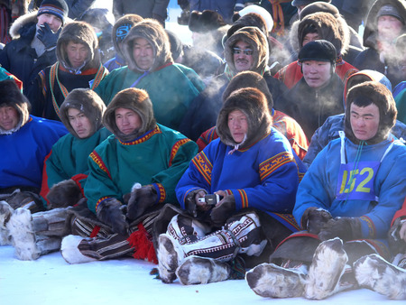 herder: Nadym, Russia - March 15, 2008: the national holiday - the Day of the reindeer herder in Nadym, Russia - March 15, 2008. A crowd of unfamiliar men Nenets sit and watch the view.