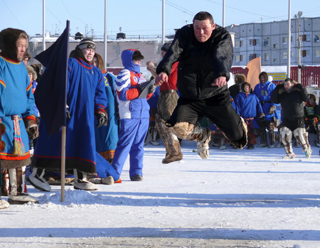 herder: Nadym, Russia - March 15, 2008: the national holiday - the Day of the reindeer herder in Nadym, Russia - March 15, 2008. Sports competitions. Unknown man jumps over obstacles.