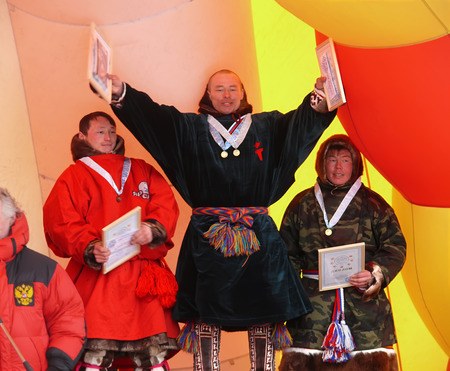 herder: Nadym, Russia - March 16, 2008: the national holiday - the Day of the reindeer herder. The ceremony of awarding the winners. Unknown men, the winners of the competitions with diplomas on stage.
