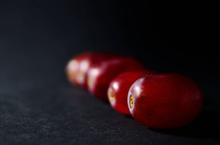 red grape berries in a row on a black background with copy space horizontal orientation