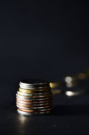getale coins stacked against the background of other coins black background vertical orientation