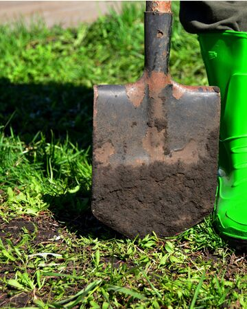 shovel dirty from the ground stands on the ground next to a rubber boot Stock Photo