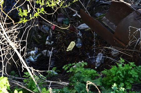pile of plastic debris in nature near the creek is a threat to the environment