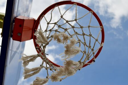 basketball ring close-up from below wind swaying mesh against blue sky Imagens