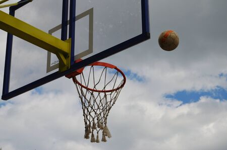 football flies to the basketball ring against the cloudy gray sky Imagens