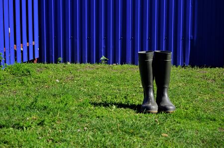 fishing boots stand on green grass against the backdrop of a blue fence in the countryside on a sunny summer day 版權商用圖片