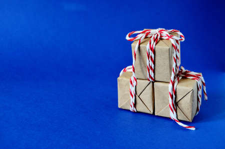 three gifts like a Christmas tree in craft paper tied with a red white rope on a blue background with a copy space, new year, to give joys, to congratulate on the new year, holiday, Christmas,