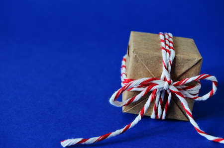 gift in craft paper tied with a red white rope on a blue background close-up with a copy space, new year, to give joys, to congratulate on the new year, holiday, Christmas, Christmas mood