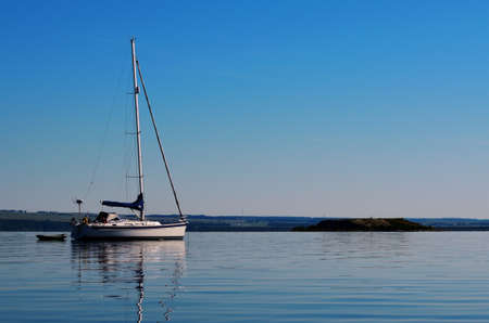 Prussian yacht is anchored near the shore near a small boat with paddles in full calm at dawn, travel, tourism, vacation, recreation, lifestyle, water transport