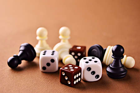 White and brown dice with white and black walking sticks with a close-up on a brown background
