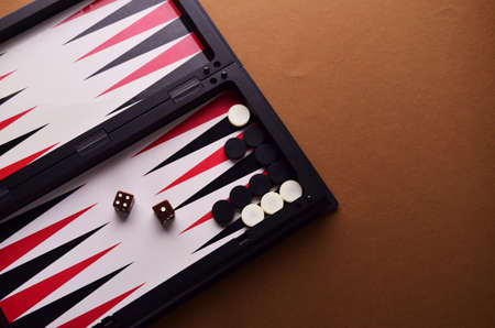 The dice are brown and white and black chips on the board