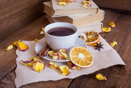 orange rose: Cup of black tea, books, dried rose petals and homemade cookies on wooden background Stock Photo