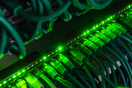 cat5: Close up of green network cables connected to black switch glowing in the dark Stock Photo