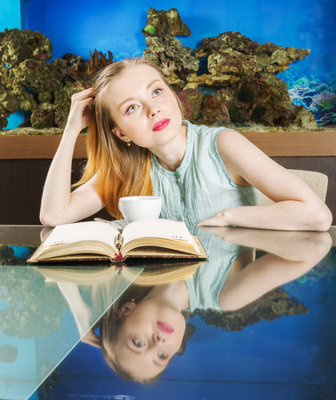 fish tank: Thoughtful young lady with book in front of fish tank