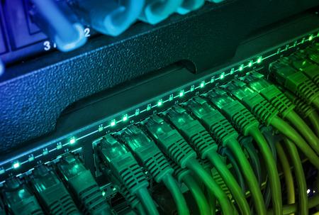 Gros plan de câbles réseau réseau vert, cordons de raccordement connectés au routeur de commutateur noir dans le centre de données brillant dans l'obscurité Banque d'images