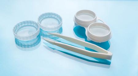 lentes de contacto: Contact lenses set with contact lenses tweezers, contact lenses plastic case with solution on blue background