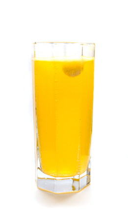 fizzy tablet: Effervescent orange tablet dissolving with bubbles in glass of water Stock Photo