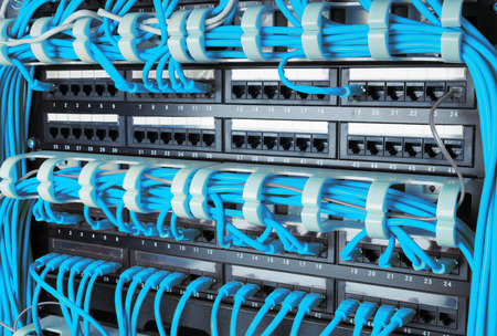 patch panel: Close up of blue network internet cables connected to router patch panel in data center Stock Photo