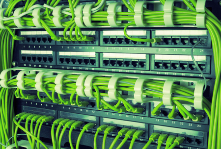 Rows of green network cables connected to router and switch hub in server room at internet data center Stock Photo