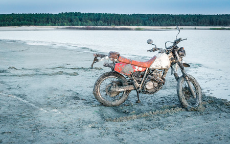 Dirty enduro off-road motorcycle standing in sands