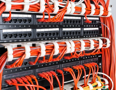 ethernet: Close up of red network ethernet cables connected to black switch in data center