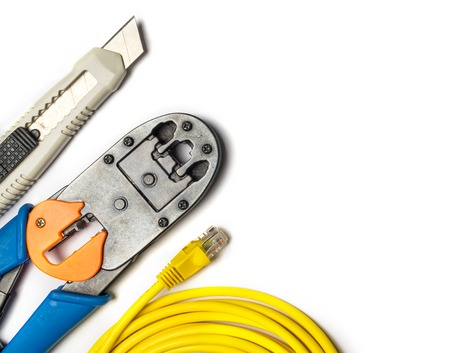Cutter, crimper, yellow patch cord on white background. Top view Stock Photo