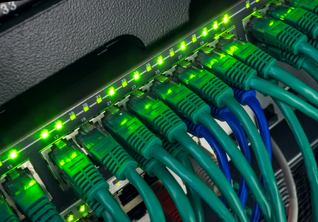 Close up of green and blue network cables connected to black switch patch panel glowing in the dark Stock Photo