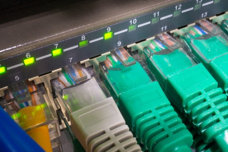 leds: Close up of green and blue network cables connected to black switch patch panel glowing in the dark Stock Photo
