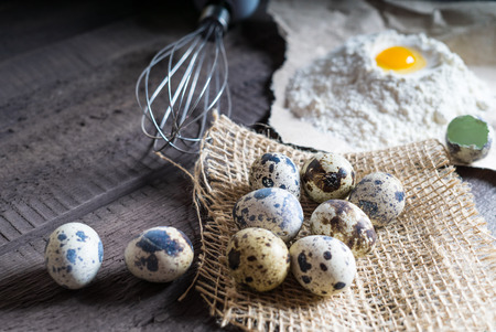 Quail eggs, flour, whisk on wooden background. Shallow deep of field, blurred, macro shot Stock Photo