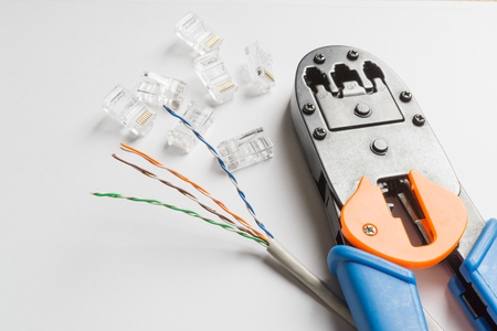 crimper: Crimper, transparent connectors and ethernet cable on white background
