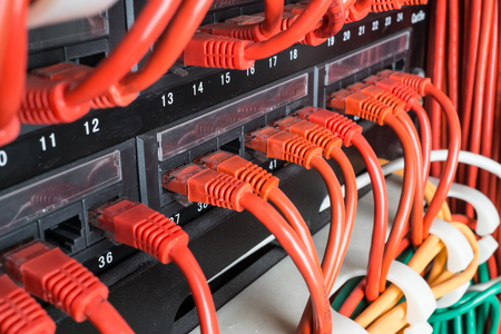 Server rack with red internet patch cord cables connected to patch panel in server room