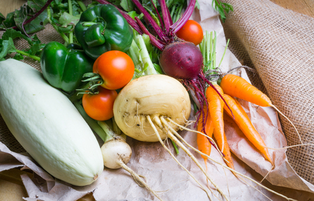 Vegetables on wooden and sackcloth background. Beetroot, carrot, tomatoes, green pepper, turnip, marrow Healthy food background
