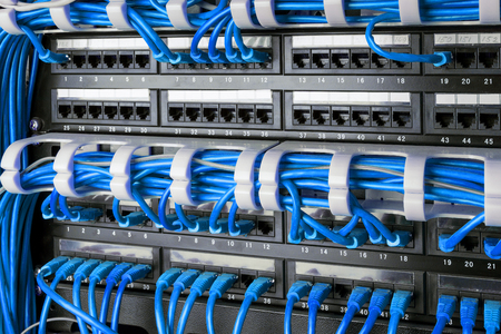 Network panel, switch and internet cable in data center. Network switch and blue ethernet cables, Data Center Concept. Stock Photo