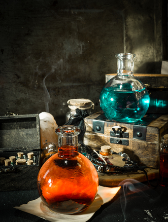 Blue and red magic potions with smoke. Magical concept with wooden box