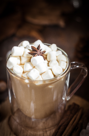 Hot coffee with milk in a glass with double walls with marshmallow and anise star. Brown, Selective focus