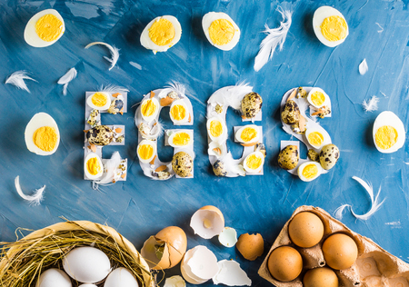 Chicken and quail eggs with word eggs on blue background with basket, feathers and box
