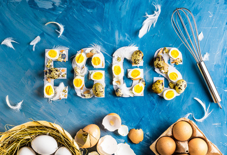 Chicken and quail eggs with word eggs on blue background with basket, feathers, whisk and box