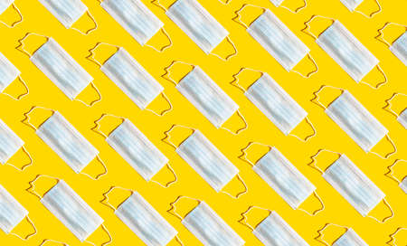 Pattern with surgical fase masks on yellow backround