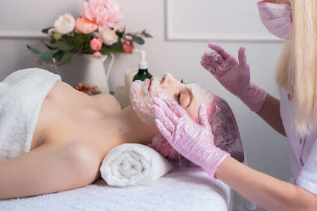 Young beautiful girl at the cosmetologists office. Cosmetic procedure, spa, rejuvenation, health. hands in pink gloves, a white towel Reklamní fotografie