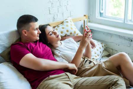 a guy and a girl lie in bed and look at the phone together. smile, plan, to trust. girlfriend shows her smartphone Stok Fotoğraf