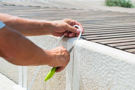 worker closes the gap between the concrete street tiles. using a white tape seal and a knife. home improvement repair.