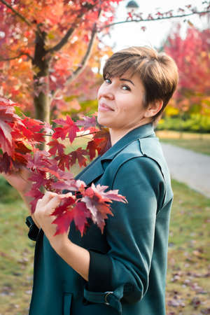 middle-aged woman walks in the autumn park. orange, red leaves. active lifestyle
