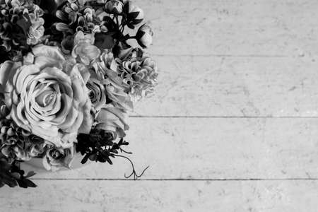 bouquet of flowers on a wooden background. black and white tinted. Selective focus. Place for text. copy spice.