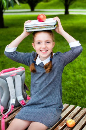 cute schoolgirl smiling, holding books and an apple on her head. happy to go back to school. redheads pigtails.