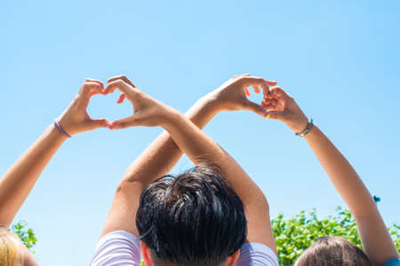female and male hands in the shape of a heart, against the background of trees and a summer park. symbol of love, trust