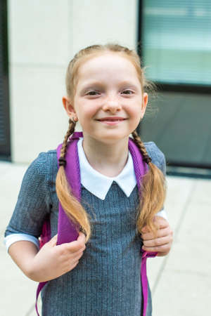 red-haired girl, schoolgirl smiles. freckled and orange braids. back to school Stockfoto